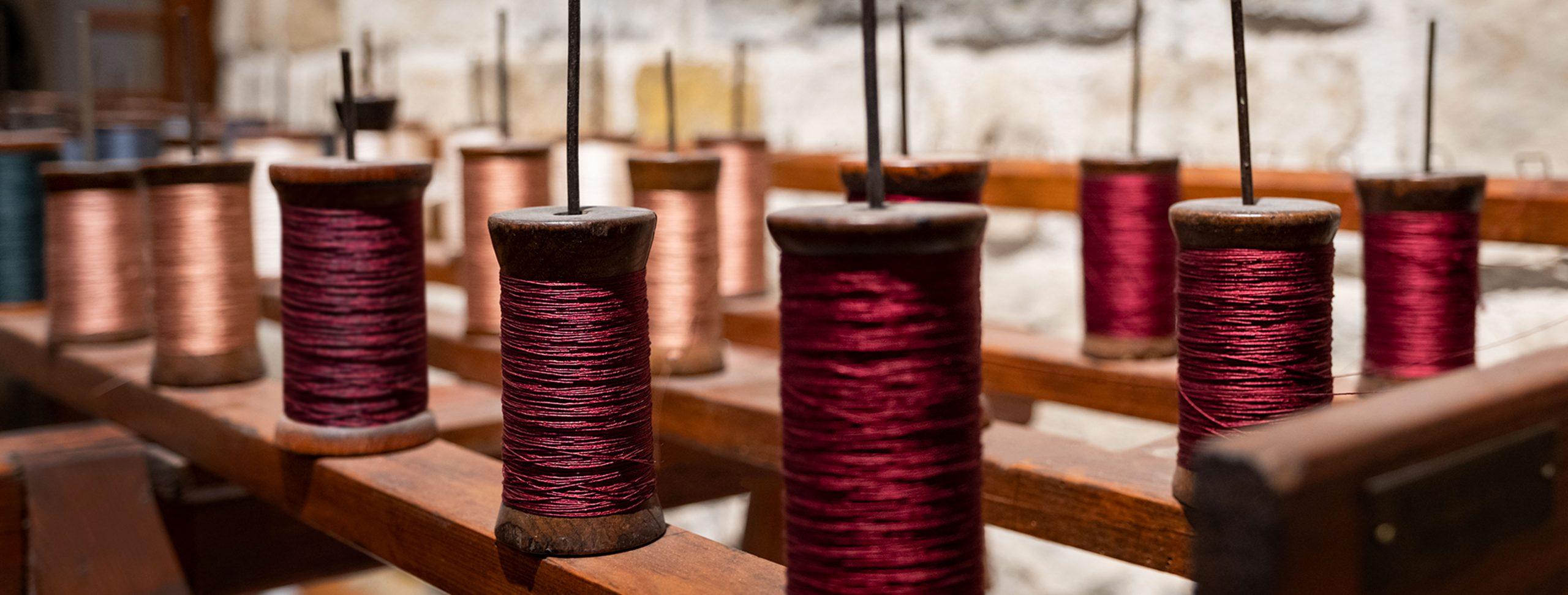 Dettaglio di diverse fili di rocchetti per tessitura.