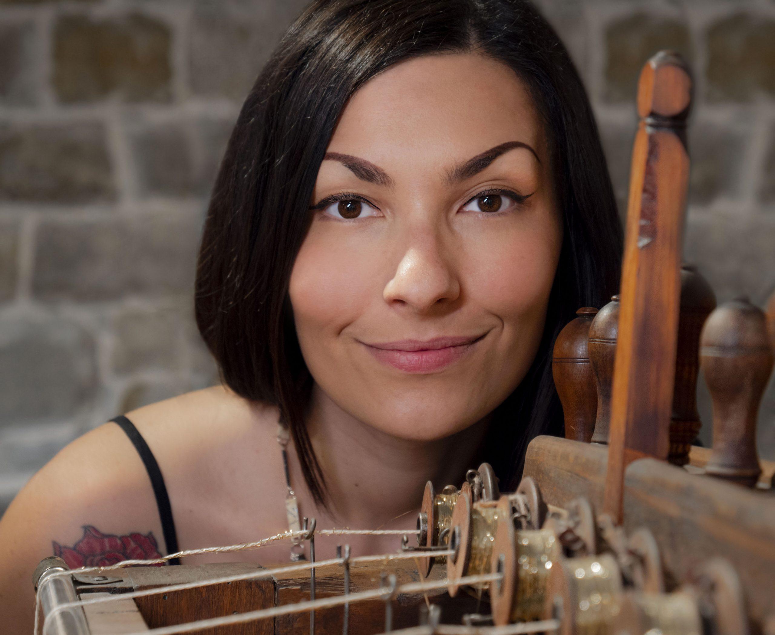 Primo piano di Chiara Corriga accanto a un telaio.