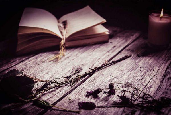 Antico libro con accanto una candela accesa e delle rose, posati su di un tavolo in legno