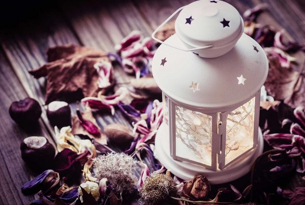 lanterna su di un tavolo ricoperto di fiori, foglie e castagne