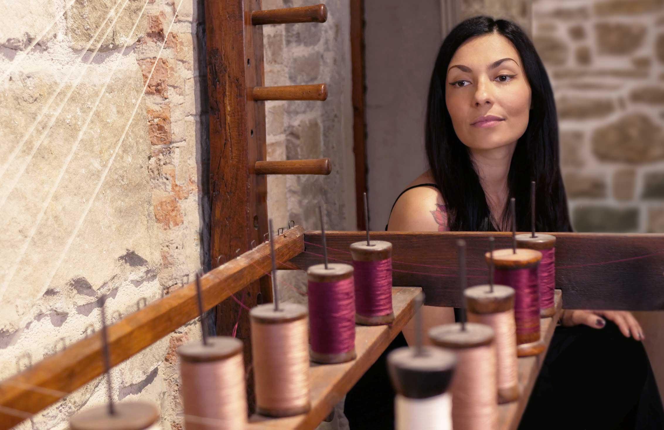 Chiara Corriga davanti a dei rocchetti di filo